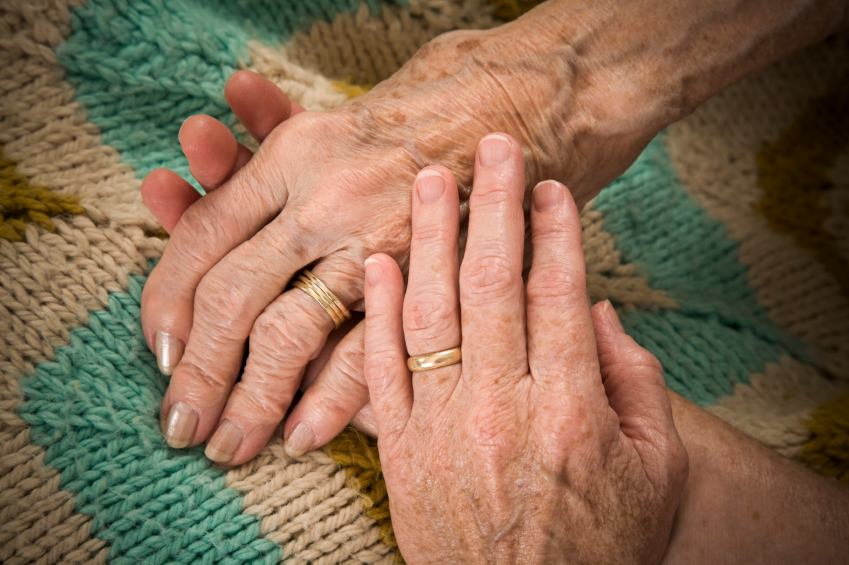 baby boomer daughter holds her senior mother's hand