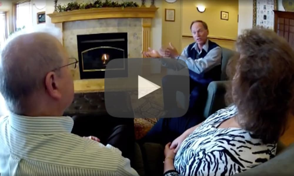 Video still of couple sitting down with care provider