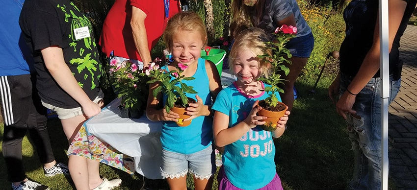 Two young girls holding potted plants